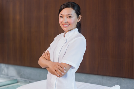 Portrait of a confident female masseur standing with arms crossed