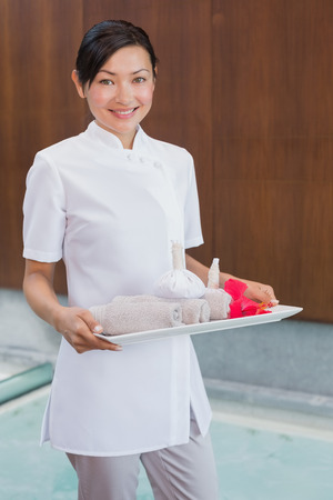 Portrait of a confident female masseur holding rolled up towels