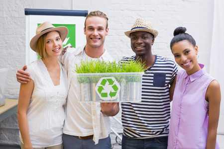 Portrait of creative business team holding plant with recycling symbol in meeting photo