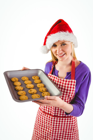 Festive blonde showing hot cookies on white background photo