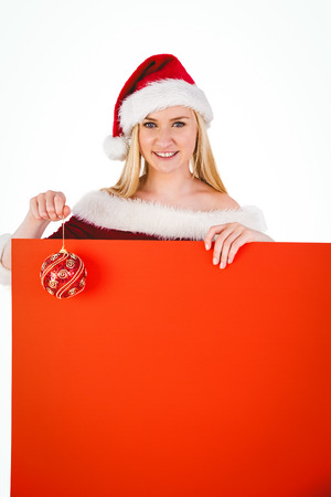 Festive cute blonde holding poster and bauble on white background photo