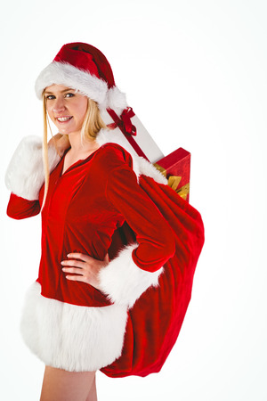 Festive blonde carrying sack of presents on white background photo