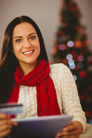 Pretty brunette shopping online with tablet at christmas at home in the living room photo
