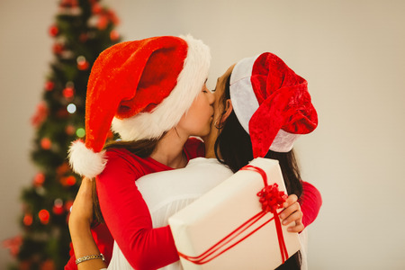 Mother and daughter hugging at christmas at home in the living room photo