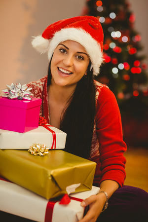Festive brunette smiling at camera at home in the living room photo