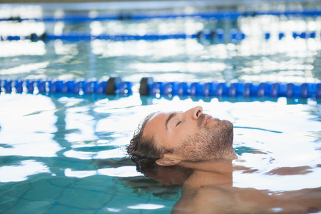 man relax: Close-up side view of a fit swimmer in the pool at leisure center Stock Photo