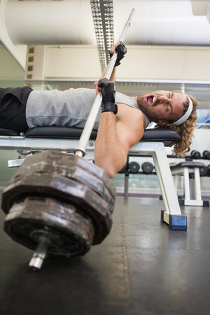 injured person: Side view of young muscular man with barbell in the gym