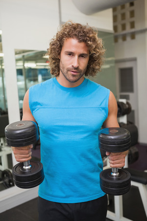 Portrait of a young muscular man exercising with dumbbells in the gym photo