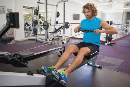 resistance: Full length of a handsome young man using resistance band in gym