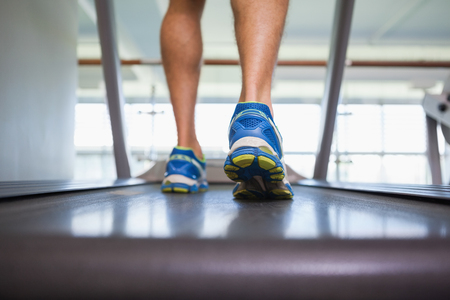 low section view: Rear view low section of a man running on treadmill in the gym Stock Photo