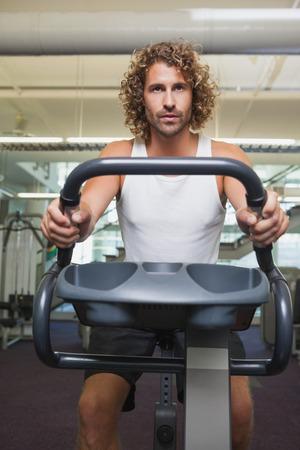 man working out: Apuesto joven Determinado hacer ejercicio en bicicleta de ejercicio en el gimnasio