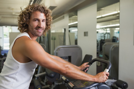 man working out: Side view portrait of a young man working out on exercise bike at the gym