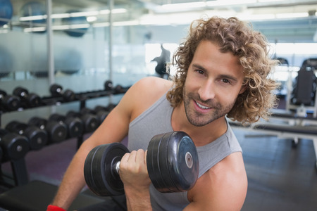 Portrait of a young muscular man exercising with dumbbell in the gym photo