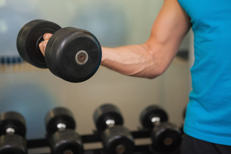 Close up mid section of man exercising with dumbbell in the gym
