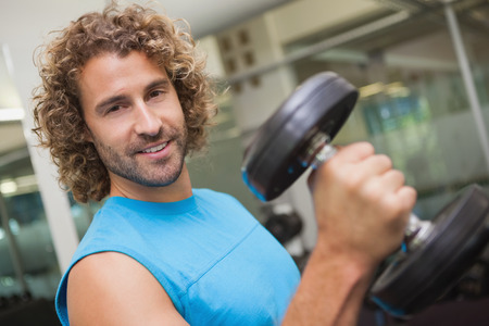 Portrait of a handsome young man exercising with dumbbell in the gym photo