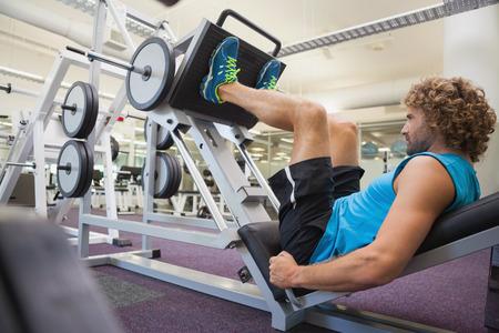 piernas hombre: Vista lateral de hombre joven haciendo press de piernas hermosas en el gimnasio