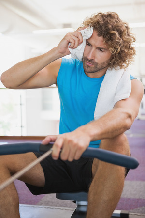Tired young man using resistance band in the gym photo