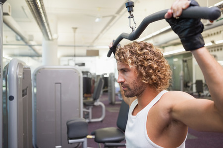 griping: Side view of a handsome young man exercising on a lat machine in gym Stock Photo