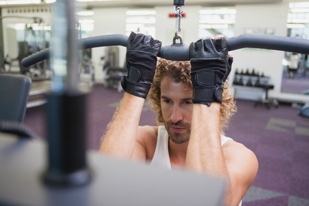 griping: Close up of a handsome young man exercising on a lat machine in gym