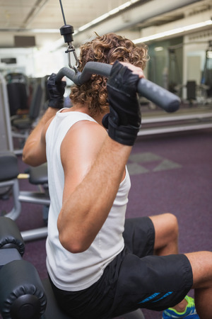 Side view of a young man exercising on a lat machine in gym