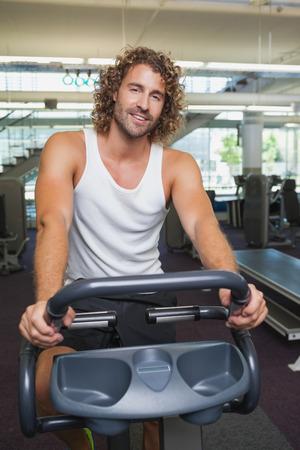 man working out: Retrato de un apuesto joven que se resuelve en la bici de ejercicio en el gimnasio