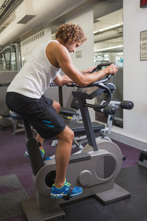 man working out: Side view of a young man working out on exercise bike at the gym