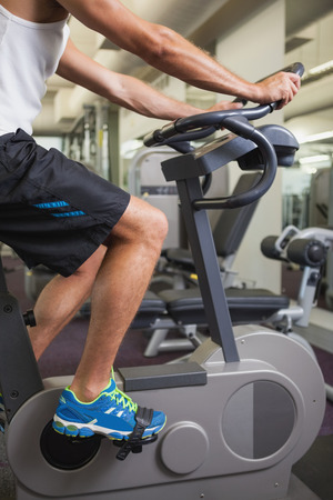 man working out: Side view of a cropped man working out on exercise bike at the gym