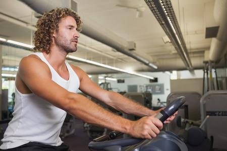 man working out: Vista lateral de un hombre joven que se resuelve en bicicleta de ejercicio en el gimnasio