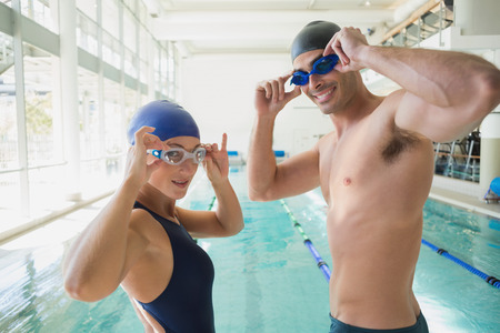 swimming pool woman: Portrait of a fit male and female swimmers by the pool at leisure center