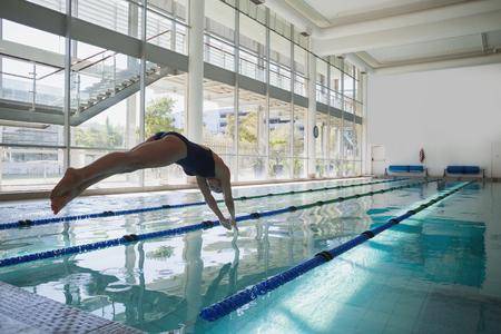 picada: Vista lateral de un salto del nadador encajar en la piscina en el centro de ocio