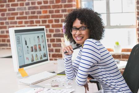 black eye: Portrait of smiling female photo editor sitting at office desk