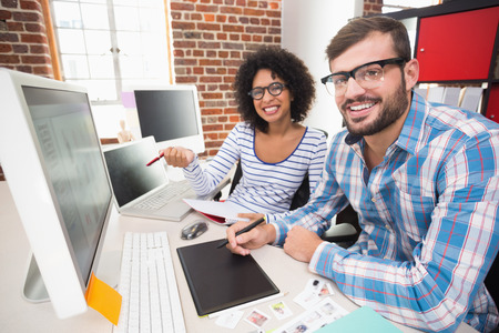 editors: Portrait of smiling photo editors using digitizer in the office Stock Photo