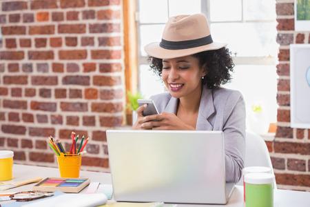 interior designer: Smiling female interior designer text messaging in the office