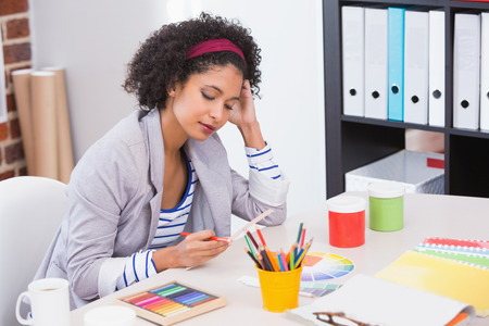 Interior designer looking at colour wheel at her desk photo