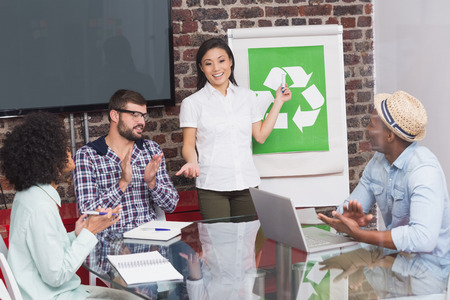 acclamation: Creative business team in meeting with recycling symbol on whiteboard Stock Photo