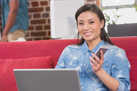 Young casual woman using laptop and mobile phone on couch in the office photo