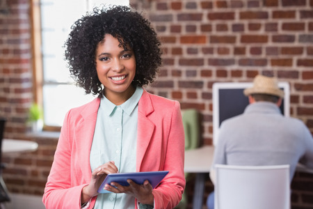 Young casual woman using digital tablet with colleagues behind in the office