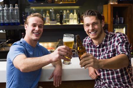 hombres jovenes: Los hombres jóvenes bebiendo cerveza juntos en el bar