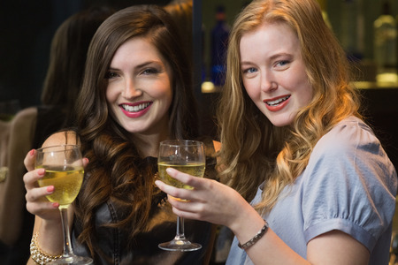 fair woman: Pretty friends drinking wine together at the bar