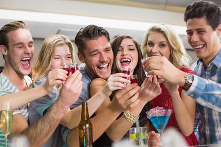 Amigos felices que tienen una copa juntos en el bar