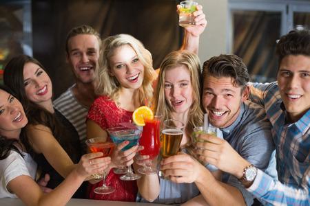 jovenes tomando alcohol: J�venes amigos que tienen una copa juntos en el bar