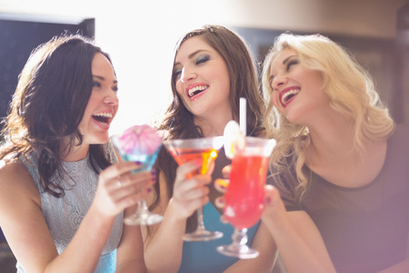 cocktail dress: Attractive friends drinking cocktails together at the bar