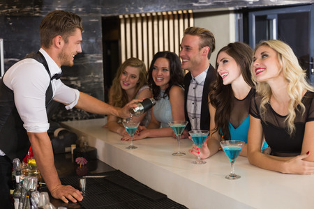 Attractive friends drinking cocktails together at the bar