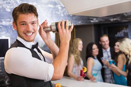 barman: Handsome barman smiling at camera making a cocktail at the bar