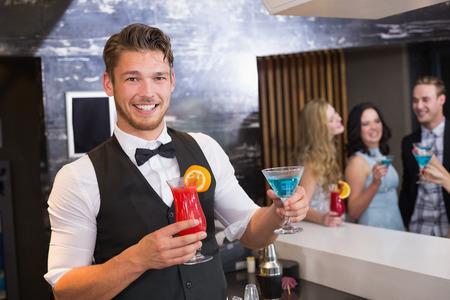 Handsome barman smiling at camera holding cocktails at the bar