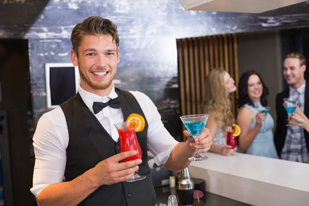 Handsome barman smiling at camera holding cocktails at the bar
