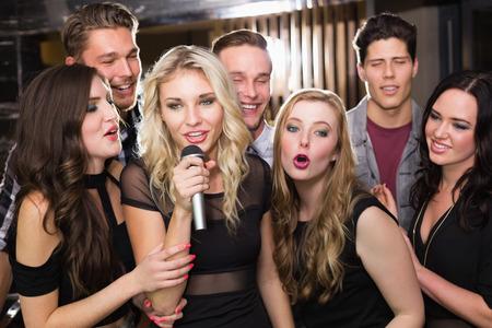 bars: Happy friends singing karaoke together at the bar
