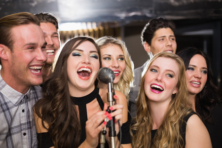 people singing: Amigos felices cantando karaoke juntos en el bar