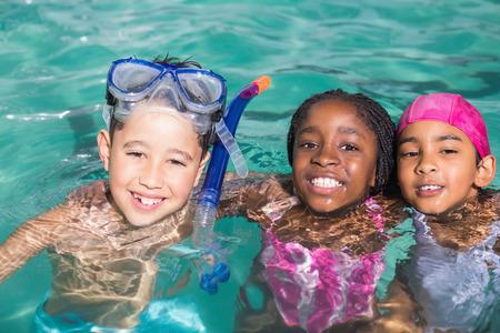 かわいい子供のレジャー センターでプールで泳ぐ