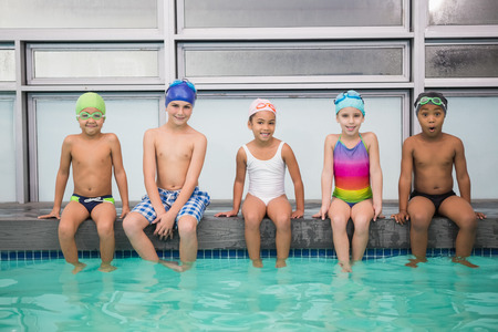 Cute swimming class smiling at camera at the leisure center